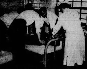 Dr. W. Van Den Bosch administering electro-shock therapy to a male patient at Norman Beatty Hospital.